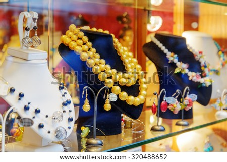 VENICE, ITALY - AUGUST 24, 2014: Original jewelry from Murano Glass in shop window on the Rialto Bridge. Beautiful beads, necklaces and earrings. Venice is a popular tourist destination of Europe. - stock photo