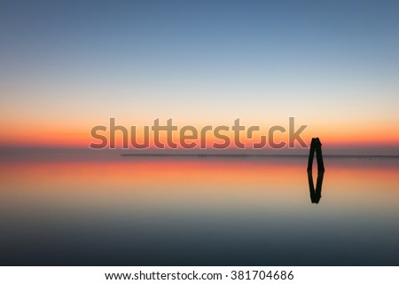 Venice, Italy - 16 December 2013: Color image showing a beautiful sunrise over the Venetian lagoon with a cloudless sky and perfect reflection in the still waters. An image of  tranquility and harmony - stock photo
