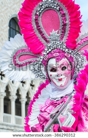 VENICE, ITALY - FEBRUARY 15, 2015:A model disguised with a white and pink costume playing violin during Venice carnival. - stock photo
