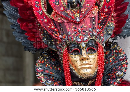 VENICE, ITALY - FEBRUARY 15, 2015: An unidentified person wearing a golden mask and a magnificent red costume at the Carnival of Venice, in Italy. - stock photo