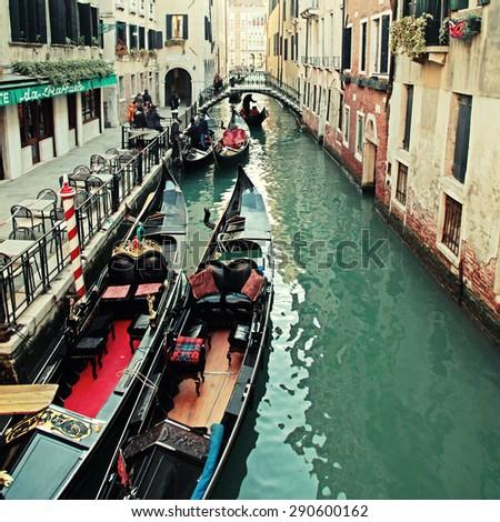 VENICE, ITALY- FEBRUARY 7, 2015: Beautiful city view and typical gondola at narrow venetian canal, Venice, Italy. Toned square image - stock photo
