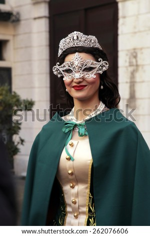 VENICE, ITALY - FEBRUARY 8, 2015: Beautiful unidentified masked woman in costume on San Marco Square during the Carnival in Venice, Italy. - stock photo