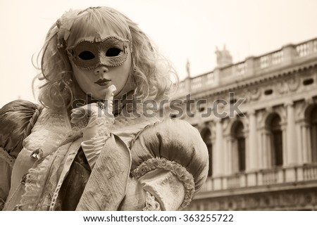 VENICE, ITALY - FEBRUARY 14, 2015: Candy Mask in St Mark's Square square during the Carnival. The Carnival in Venice is annual event which ends on Shrove Tuesday. - stock photo