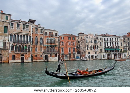 VENICE, ITALY-FEBRUARY 20, 2007: gondolier looking for tourists in the Grand canal.  Venice is a great tourists attraction with more than 27 million tourists every year. - stock photo