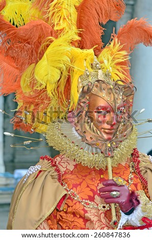 VENICE, ITALY - FEBRUARY 12: Magnificent carnival mask in orange and yellow with ostrich plumes the 2015 Venice Carnival:  February  12, 2015 in Venice, Italy