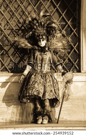 VENICE, ITALY - FEBRUARY 16, 2015: Peacock mask in sunlight near Doge's Palace in St Mark's Square during traditional Carnival. The Carnival in Venice is annual event which ends on Shrove Tuesday.