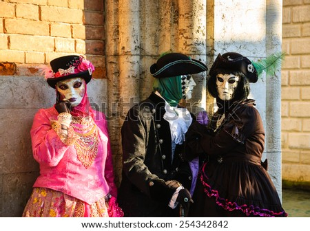 VENICE, ITALY - FEBRUARY 16, 2015:Three masks in St Mark's Square square during the traditional Carnival. The Carnival in Venice is annual event which ends on Shrove Tuesday. - stock photo