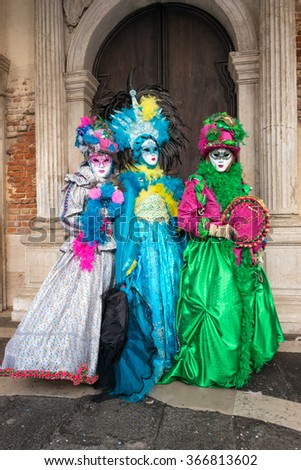 VENICE, ITALY - FEBRUARY 15, 2015: Three models disguised with colorful carnival costumes at the Carnival of Venice in Italy.