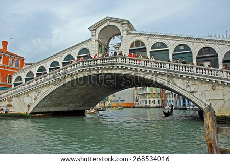 VENICE, ITALY-FEBRUARY 14, 2007: tourists looking at the Grand Canal from the famous Rialto bridge. Venice is a great tourists attraction with more than 27 million tourists every year. - stock photo