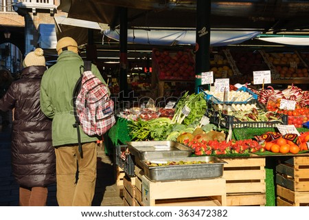 VENICE, ITALY - FEBRUARY 16, 2015: Tourists visiting the Rialto market. This famous colorful market is located alongside the Grand Canal near the Rialto Bridge.