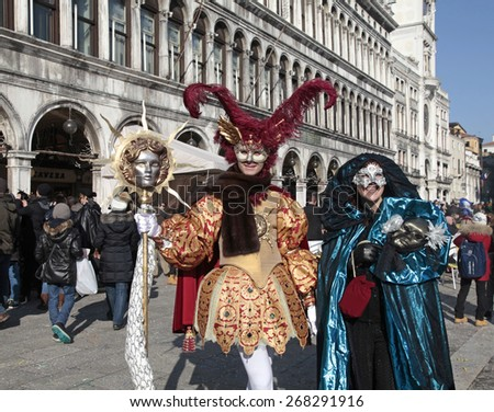 VENICE, ITALY - FEBRUARY 8, 2015: Two unidentified masked persons in beautiful medieval costume on San Marco Square during the Carnival in Venice, Italy. - stock photo