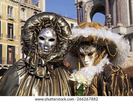 VENICE, ITALY - FEBRUARY 8, 2015: Two unidentified masked persons in golden costume on San Marco Square during the Carnival in Venice, Italy. Horizontal image - stock photo