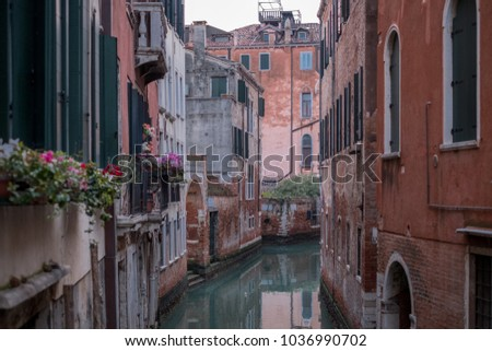Venice Italy, February 2018. Typical canal scene in Venice. showing red coloured buildings with green shutters overlooking the canal.
