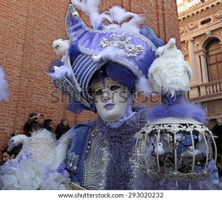 VENICE, ITALY - FEBRUARY 8, 2015: Unidentified masked person in magnificent lilac medieval costume on San Marco Square during the Carnival in Venice, Italy. - stock photo
