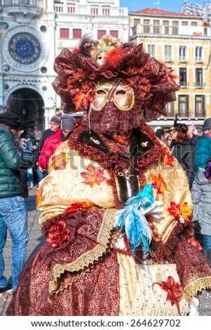 VENICE, ITALY - FEBRUARY 8, 2015: Unidentified masked woman in costume on San Marco Square during the Carnival in Venice, Italy. - stock photo