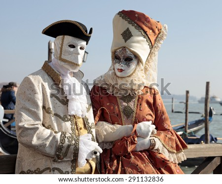 VENICE, ITALY - FEBRUARY 8, 2015: Unidentified persons in Venetian mask and romantic costumes at St. Marco Square, Carnival of Venice, Italy - stock photo