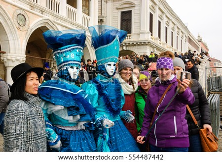 VENICE, ITALY - FEBRUARY 14, 2015:Young tourists taking selfie with couple of masks at San Marco square during the Carnival. The Carnival in Venice is annual event.