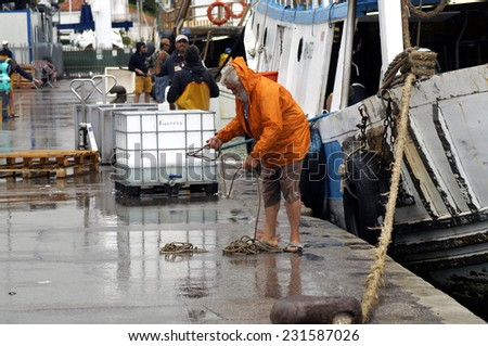 VENICE,  ITALY -10 JULY 2014: a fisherman working the nets on the dock of the port after spending the night at sea on his fishing boat