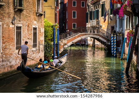VENICE, ITALY - JULY 2013: Gondola with tourists sailing on a typical Venetian water street on July 26, 2013 in Venice Italy. - stock photo