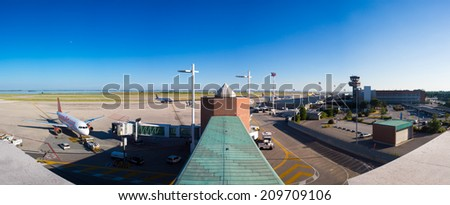 VENICE, ITALY - JUNE 09: Full panoramic view of planes parked at the passenger terminal of Marco Polo Airport, Venice on June 09, 2014. The airport is popular with tourists to the region. - stock photo