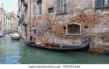 VENICE, ITALY - 26 JUNE, 2014: Tourists float in gondola on canal in Venice - stock photo