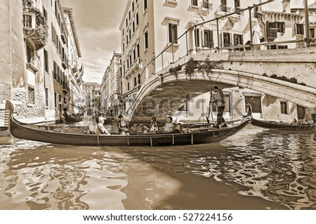 VENICE, ITALY - JUNE 26, 2014: Tourists travel on gondolas at canal Venice, Italy . Gondola trip is the most popular touristic activity in Venice. The Old style sepia.