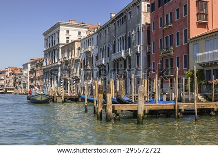 VENICE, ITALY - JUNE 30, 2015: View from Grand Canal on wooden piers and surrounding buildings, colored photo.