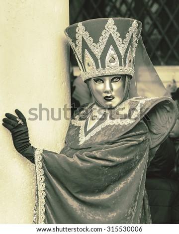 VENICE, ITALY - MAR 04, 2014: Unrecognizable persons wearing carnival costume (mask) in Saint Mark square in Venice, Italy. In 2014 the Carnevale di Venezia was held 15 Feb - 04 Mar (stylized retro) - stock photo