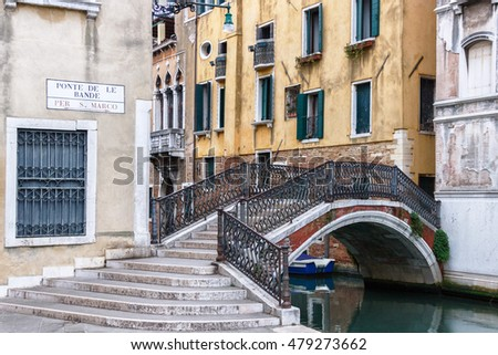 VENICE, ITALY - MARCH 31, 2016: A yellow Venetian street corner with an arch railed bridge over a canal.