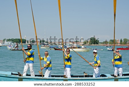 VENICE, ITALY - MAY 17, 2015:  Five Venetian men on their rowing boat holding long oars straight up during the historic Festa della Sensa ceremony where the city marries the sea.   - stock photo