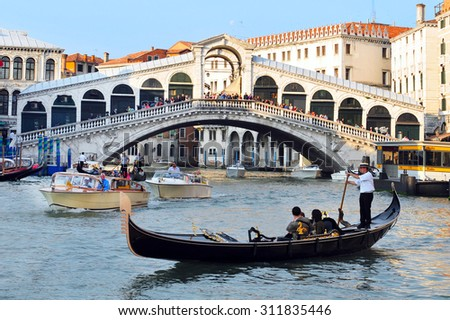 VENICE, ITALY - MAY 01 2011:Gondolas sail on the Grand Canal in Venice, Italy under the Rialto bridge.About 30 million people visit the city each year. - stock photo