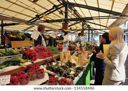 VENICE, ITALY - MAY 02 2011:Shopping in the Rialto Market in Venice, Italy.In Italy it's forbidden to touch products on display and the vendor is choose and give their best products to the customer - stock photo