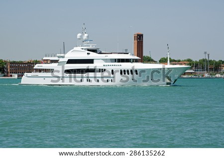 VENICE, ITALY - MAY 17, 2015:  The luxury motor yacht Bacarella sailing across the Venice lagoon with Saint Elena church tower in the background. - stock photo