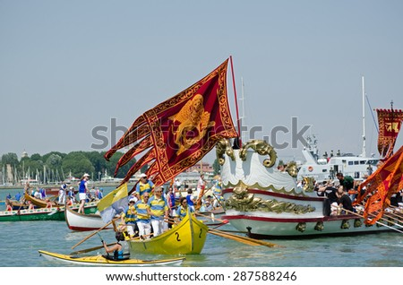 VENICE, ITALY - MAY 17, 2015: The red and gold flag of Venice flying in the middle of the Festa della Sensa ceremony where Venetians gather in boats near Lido to see the City married to the Sea. - stock photo