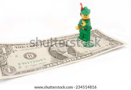 Venice, Italy - November 27, 2014: Robin Hood (as Lego figure) standing on  an American one dollar bill, November 27, 2014 in Venice, Italy - stock photo