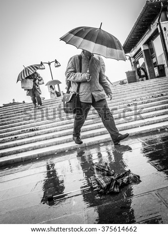 VENICE, ITALY -  20 OCTOBER 2011:  Monochrome image of a man rushing down steps with an umbrella through the streets of Venice in the rain. Contemporary street scenes of Venice, Italy - stock photo