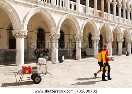 Venice, Italy - September 29, 2017: Two DHL postmen delivering parcels on the Piazza San Marco in Venice in front of Doge´s Palace.