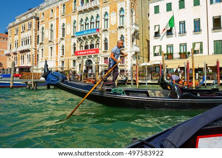 Venice, Italy - 8 September, 2016: Venetian gondolier punting gondola through waters of Venice Italy