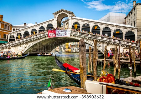 VENICE, ITALY - SEPTEMBER 01, 2013: View of famous Grand Canal and Rialto Bridge (Ponte di Rialto) in Venice, Italy with traditional gondolas and boats on a sunny day - stock photo