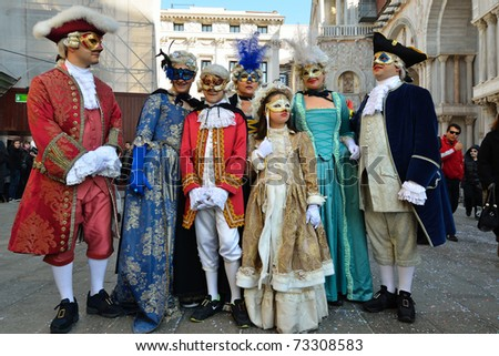 VENICE - MARCH 7: A family masked in costume in St. Mark's Square during the Carnival of Venice on March 7, 2011. The 2011 carnival was held from February 26th to March 8th. - stock photo