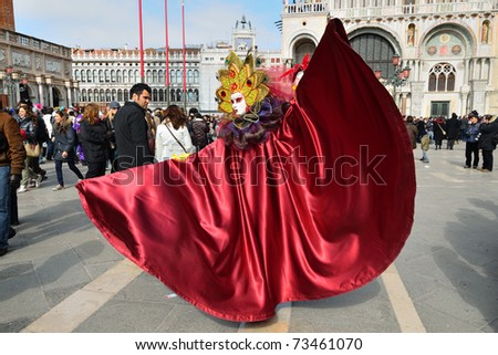 VENICE - MARCH 7: An unidentified masked person in costume in St. Mark's Square during the Carnival of Venice on March 7, 2011. The 2011 carnival was held from February 26th to March 8th. - stock photo