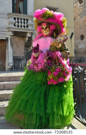 VENICE - MARCH 7: An unidentified masked person in costume on the bridge via Venice canal during the Carnival on March 7, 2011. The 2011 carnival was held from February 26th to March 8th. - stock photo