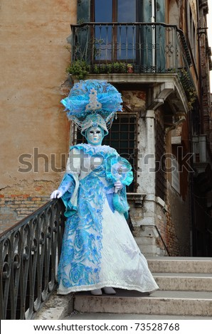VENICE - MARCH 7: An unidentified masked person in costume on the bridge via Venice canal during the Carnival on March 7, 2011. The 2011 carnival was held from February 26th to March 8th.