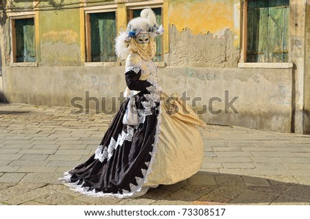 VENICE - MARCH 7: An unidentified masked person in costume on the street of Venice during the Carnival on March 7, 2011. The 2011 carnival was held from February 26th to March 8th. - stock photo