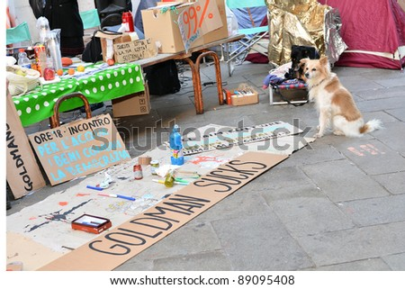 VENICE - NOVEMBER 17 2011: A small dog and signs from the protest camp of the Occupy Venice movement sit in front of the Italian Bank in Venice, Italy on Nov. 17, 2011. It is part of the global Occupy Wall Street movement. - stock photo
