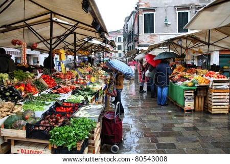 VENICE - SEPTEMBER 16: Shoppers at a farmers market on September 16, 2009 in Venice, Italy. According to Euromonitor Venice was the 26th most visited city in the world in 2006. - stock photo