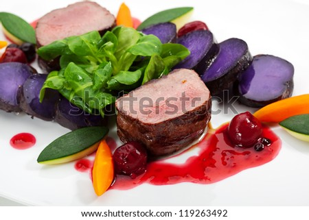 Venison Meat with Carrots, Zucchini, Herbs and Potato. With Sauce and Red Berries - stock photo