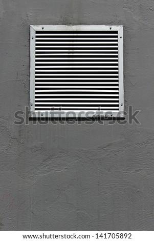 Vent window on gray concrete wall - stock photo