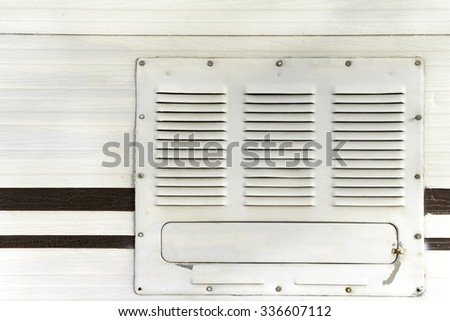Vented utility cover and faux wood grain sheet metal camper exterior - stock photo