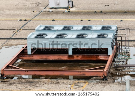 Ventilation fans, pipes, red steel bars, and other industrial machinery on flat roof top. Puddles of standing water are under machinery, and part of girder is wet. - stock photo